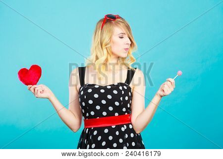 Woman Blonde Lovely Girl Wearing Dotted Dress Holding Red Heart Love Symbol And Lollipop Candy. Vale