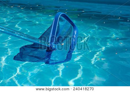 Swimming Pool With Blue Ripple Water During Clean Maintenance. Pool Net Cleaner Close Up.