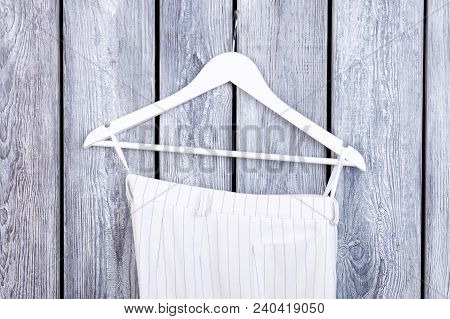 Female Clothes On Hanger, Wooden Background. Female White Classy Trousers Hanging On White Hanger. W