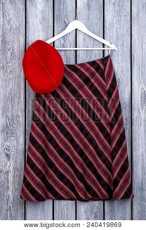 Women Striped Skirt Hanging On Hanger. Female Red Beret And Skirt, Wooden Background. Female Classy