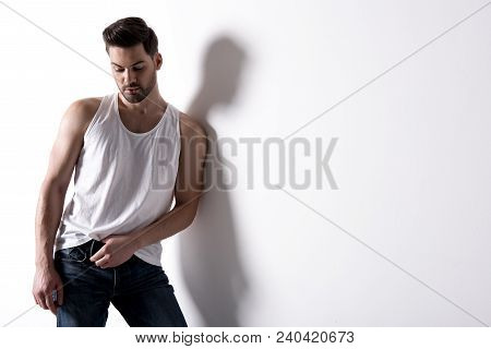 Young Pleasant Trendy Man With Stubble Is Leaning On White Wall And Enjoying His Appearance. Copy Sp