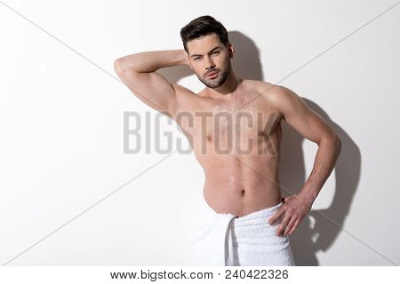 Portrait Of Pensive Young Bearded Man Is Standing With Towel On His Hips And Looking At Camera Thoug