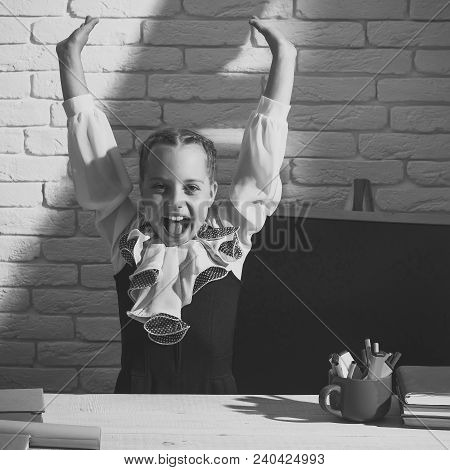 Girl Sits At Desk With Colorful Stationery And Books. Schoolgirl With Cheerful Face Near Blank Black