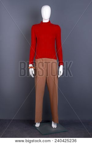 Female Mannequin In Red Sweater And Trousers. Women Red Turtleneck Pullover And Brown Trousers. Ladi