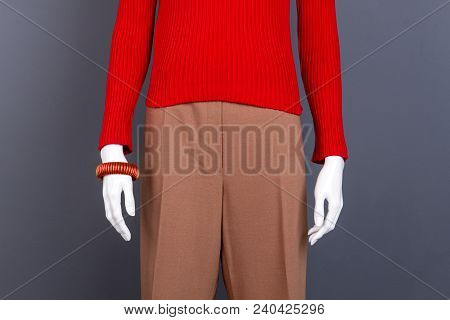 Close Up Red Sweater And Accessory. Female Mannequin Wearing Red Pullover And Brown Pants, Grey Back