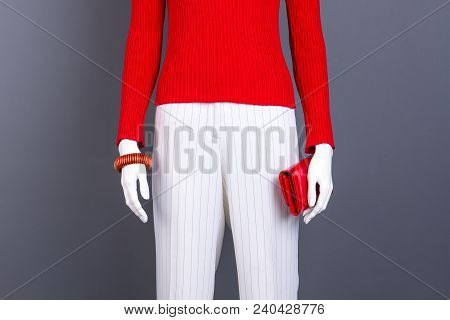 Mannequin with red sweater, bracelet and wallet. Red pullover and white trousers for women. Feminine stylish garment and accessories. poster
