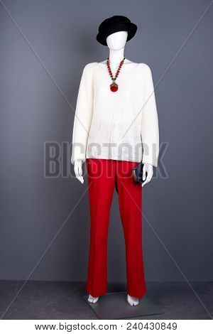 Mannequin In White Women Sweater And Red Trousers. Female Mannequin With Black Hat, Necklace And Pur