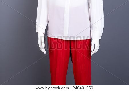 White blouse and red trousers, cropped image. Female mannequin dressed in classy women garment close up, grey background. poster
