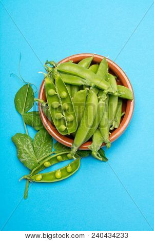 Fresh Green Ripe Sugar Snaps, Sweet Peas In Bowl Copy Space Close Up On Blue Background