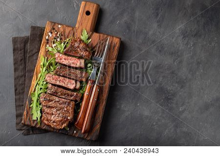 Closeup Ready To Eat Steak New York Beef Breeds Of Black Angus With Herbs, Garlic And Butter On A Wo