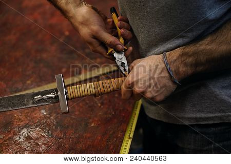 Blacksmith Fastens Leather Winding Of Sword. Man Is Working In Workshop. He Fixes The Leather Band W