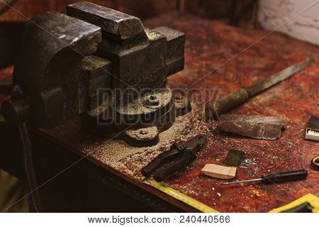 Vices, pliers, files and awls lie on workbench in carpentry workshop. Tool for manual labor poster