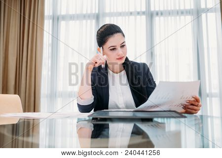 Pensive Thoughtful Business Woman Reading A Document In Office Workspace. Manager Analyzing Informat