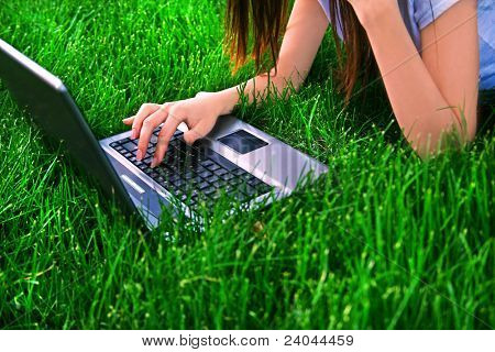 woman connecting the internet with her laptop at the park (above view)