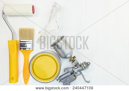 Paint Roller, Brush, Safety Glasses, Compressor Paint Sprayer, Yellow Paint Can On White Wooden Back