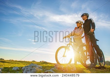 Cyclist Couple With Mountain Bikes Standing On The Hill Under The Evening Sky And Enjoying Bright Su
