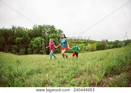 A Woman With Children Runs Along The Green Grass. Mom Holds Her Sons By The Hands And Laughs. A Boy