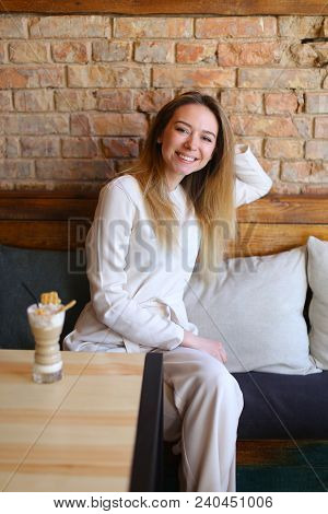 Young Woman Having Rest In Coffee House, Beautiful Smiling Fair-haired Relaxed Lady Wearing White Bl