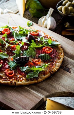 Fresh Italian  Pizza On Wood. Pizza With Cheese, Salami And Tomatoes. Fast Food. Rustic Pizza