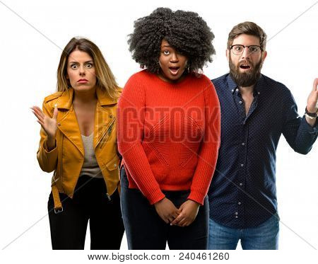 Group of three young men and women scared in shock, expressing panic and fear