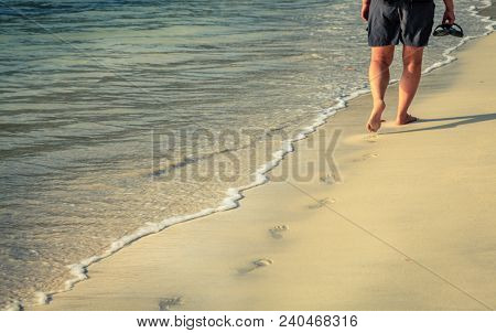 A person walkng along a sand beach on an island in BVI