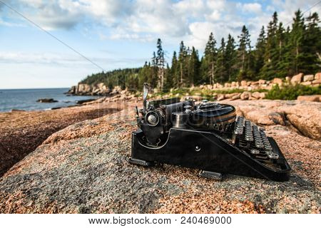 ACADIA NP - JULY 12: Antique typewriter near ocean on granite rock with blue sky Acadia National Park, Maine seein July, 12, 2013.