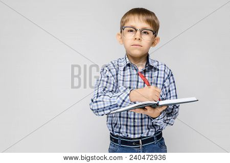 Portrait Of A Boy On A Gray Background. A Boy With Glasses. The Boy Holds A Notebook And A Red Pen I