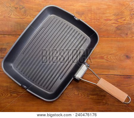 Top View Of Empty Grill Pan Rectangular Shape With Wooden Handle, Non-stick Coating And A Series Of