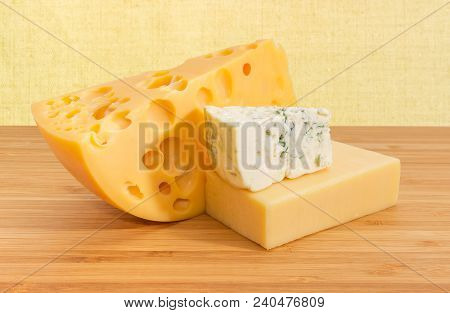 Pieces Of Medium-hard Swiss Cheese, Hard Cheese, Blue Cheese On The Bamboo Wooden Surface