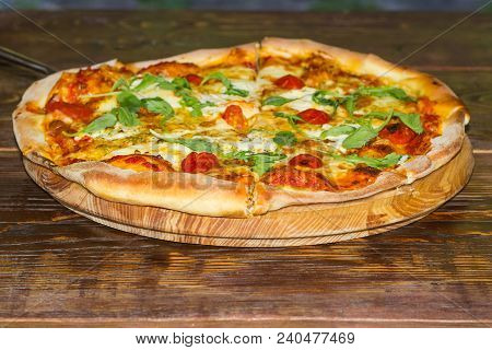 Cooked Round Pizza With Tomatoes, Cheese And Arugula Closeup On The Wooden Stand On An Old Wooden Ru