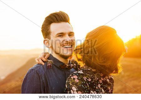 Couple In Love Happily Walks And Embrace On The Sunset Background