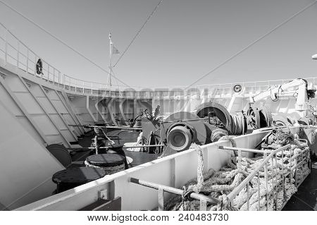Ship Stern Deck With Nautical Ropes, Mooring Winch, Hook And Lifebuoy On Sunny Blue Sky Background I