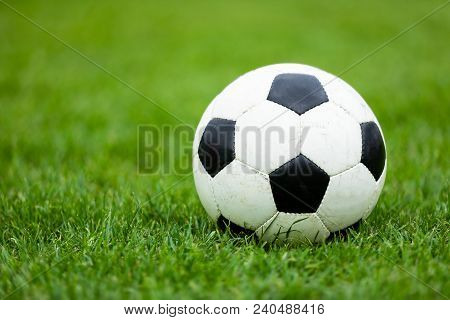 Classic Soccer Football Ball On Soccer Pitch. Green Grass Soccer Field. Soccer Turf In The Backgroun