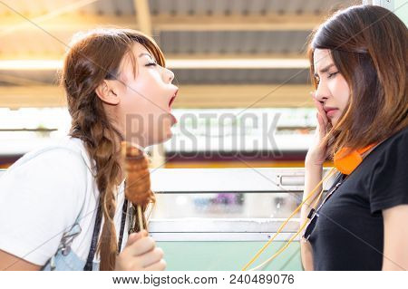 Lovely Girl Is Using Hand Close Her Nose Because Her Friend Persecute And Blow Her Bad Breath To Her