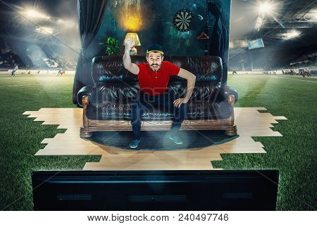 Ardent Fan Sitting On The Sofa And Watching Tv In The Middle Of A Football Field. Soccer Football Co