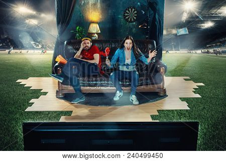 Ardent Fans Sitting On The Sofa And Watching Tv In The Middle Of A Football Field. Soccer Football C