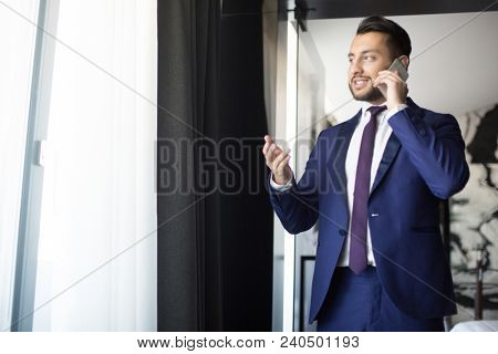 Young and confident broker in formalwear standing by office window, looking through it and talking to client or partner by smartphone