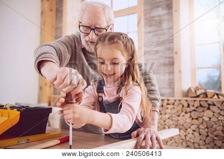 My Workshop. Positive Cheerful Man Holding A Screwdriver While Working Together With His Granddaught