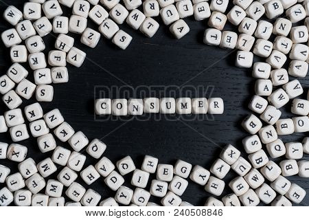 Word Consumer On Wooden Cubes On A Black Wooden Table With Copy Space