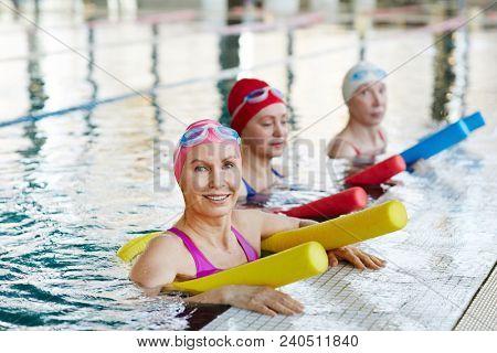 Active senior women in swimwear holding equipment for water aerobics while training in swimming-pool