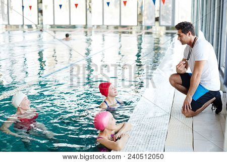 Young swimming trainer in sportswear talking to mature females in swimming-pool during training