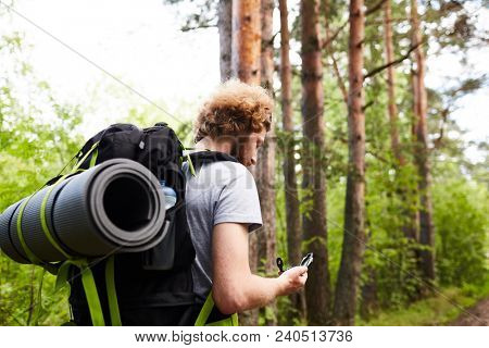 Young tripper with backpack and compass looking for right way to his camp