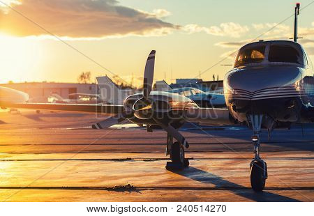 Small Aviation: Private Jet Is Parked On A Tarmac In A Beautiful Sunset Light