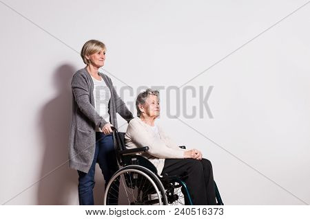 Studio Portrait Of A Happy Senior Woman In Wheelchair With A Carer. Copy Space.