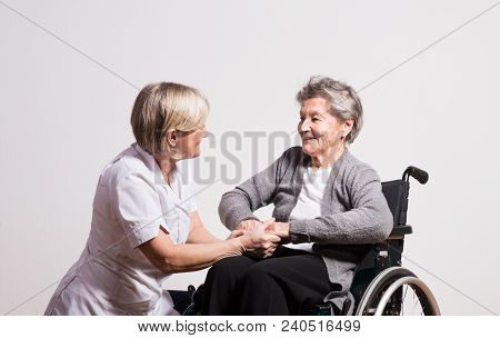 Studio Portrait Of A Senior Nurse And An Elderly Patient In Wheelchair. Two Women Talking.