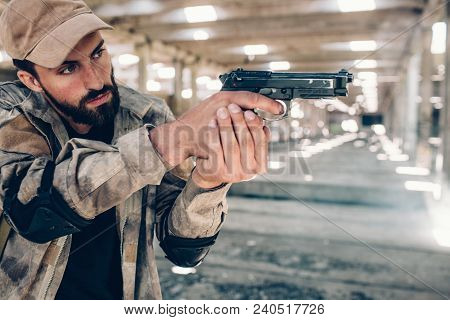 Serious And Concentrated Guy Is Taking Aim. He Is Doing That With Both Hands. Also Man Wears Special