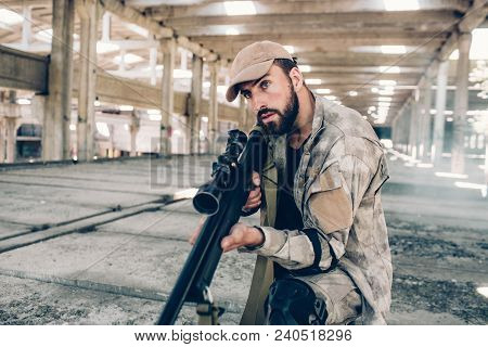 Serious Guy Is Paying Attention To Sounds In Big Empty Building. He Is In Hangar. Soldier Is Holding