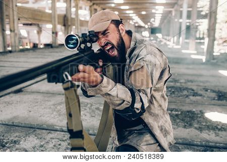 Horizontal View Of Military Soldier Screaming And Yelling. He Is Taking Aim By Using Big Rifle. Man