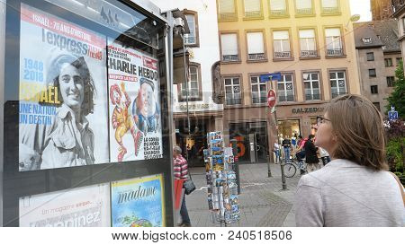 Strasbourg, France - May 5, 2018: Woman Reading Newspaper Covers In French City Of Strasbourg On A P