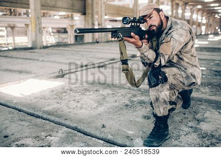 Warrior Is Standing On One Knee And Taking Aim. He Looks Very Serious And Concentrated. Guy Is Holdi